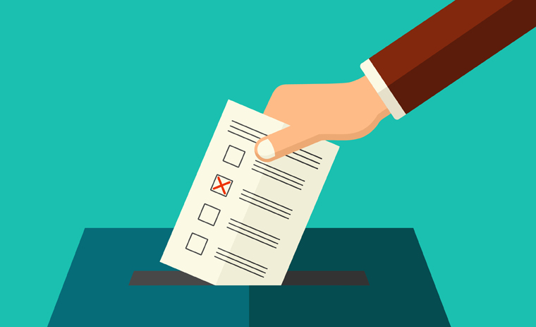A hand placing a ballot in a ballot box / Une main déposant un bulletin de vote dans une boîte de vote