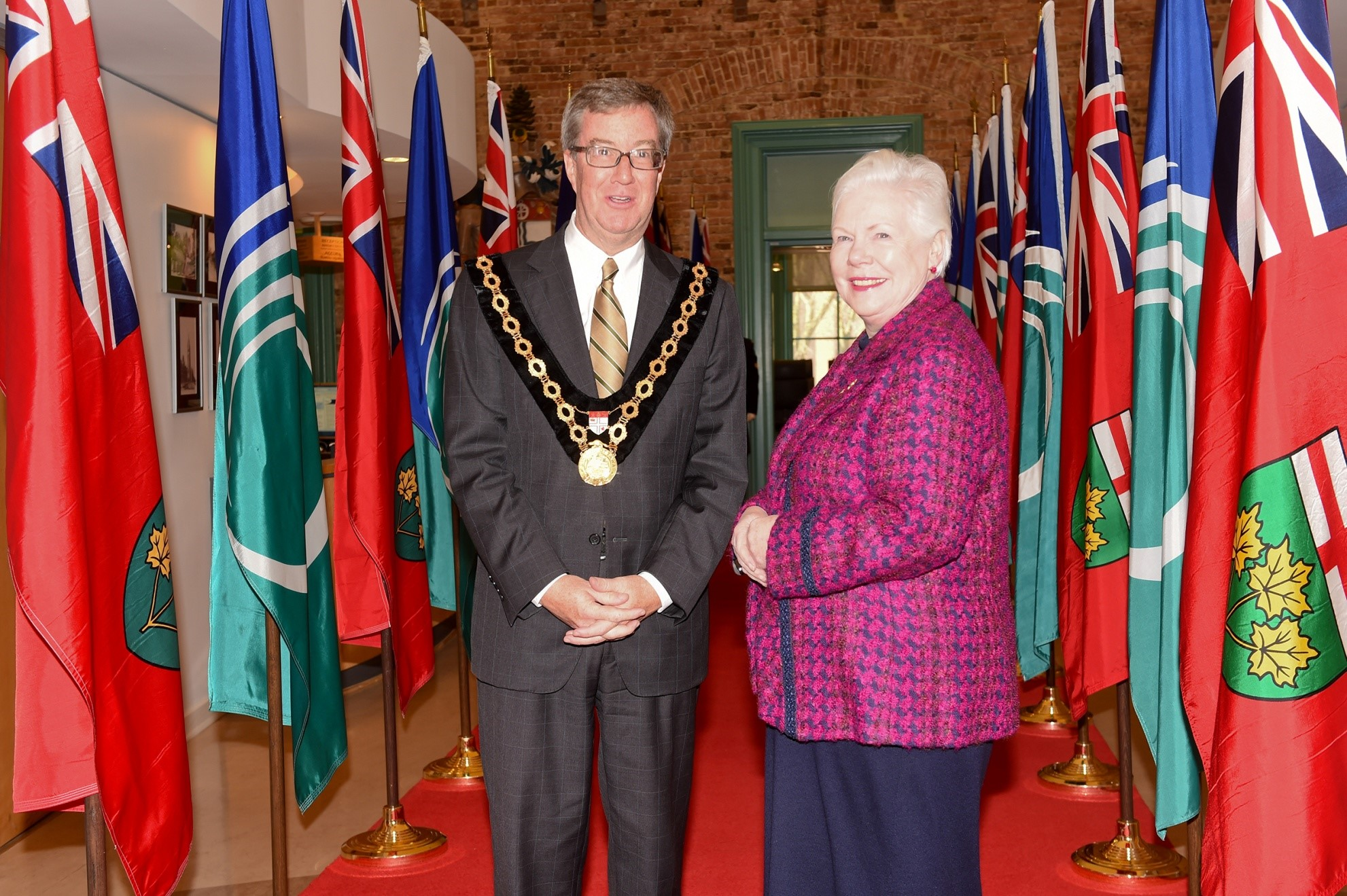 Mayor Jim Watson and Lieutenant Elizabeth Dowdeswell standing by flags