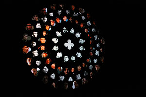 Video installation that resembles a rose window in a cathedral. Each hole in the window plays a video of a cinematic portrayal of Joan of Arc.