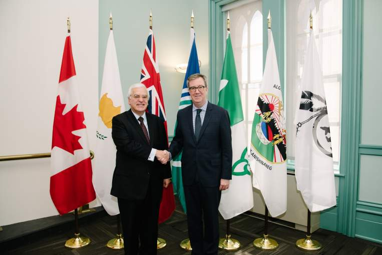 Mayor Jim Watson and Ambassador of Cyprus standing in front of flags