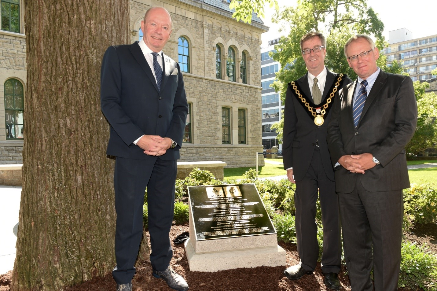 Mayor Jim Watson and Ambassadors standing beside plaque at Dedication Ceremony