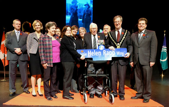 Members of the Rapp Family and dignitaries holding the street sign for Helen Rapp Way