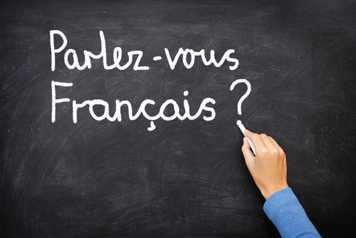 Teacher writing Parlez-vous Francais? (do you speak French?) on chalkboard.