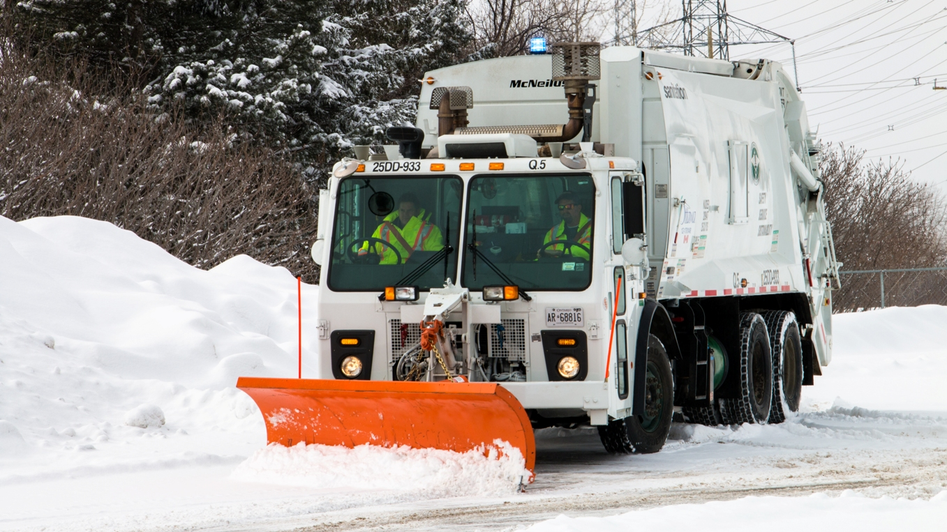 A garbage truck with a snow plow
