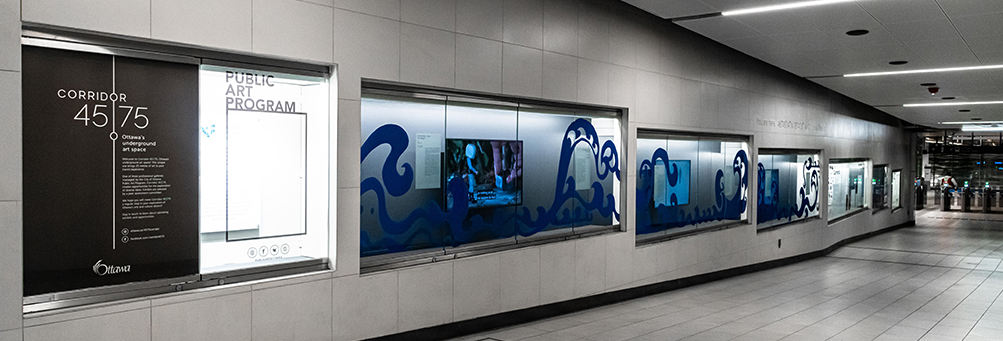 image shows an installation view of an exhibition in a long corridor of bright blue and white landscapes images.