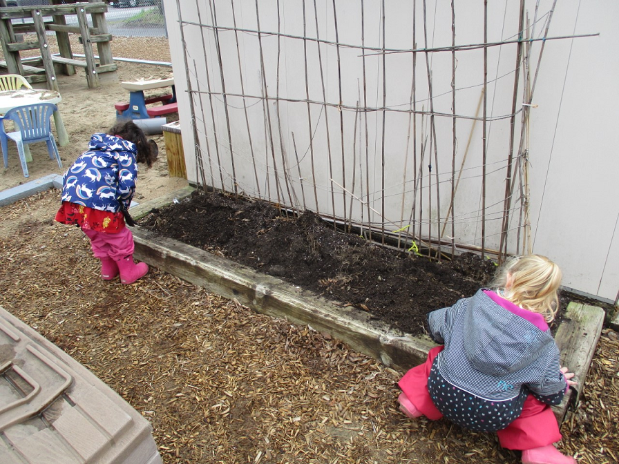 Two kids in spring jackets and rubber boots search for worms in a daycare playground.