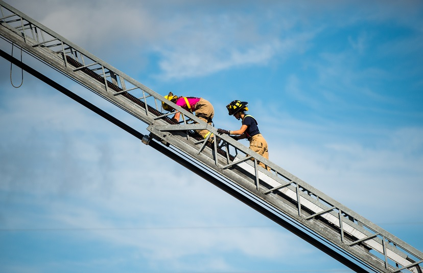 Two firefighters climbing a ladder