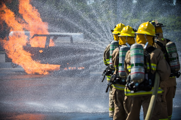 Firefighters spray water on a fire