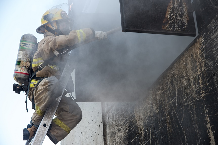 Firefighter on a ladder, surrounded by smoke
