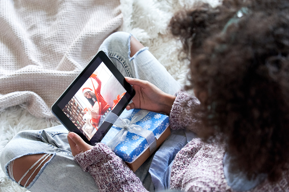 A black girl wearing a knit sweater and blue jeans with a giftwrapped package in her lap holds a tablet, meeting virtually with a friend.