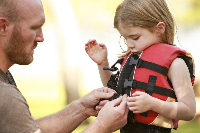 Man putting lifejacket on a girl
