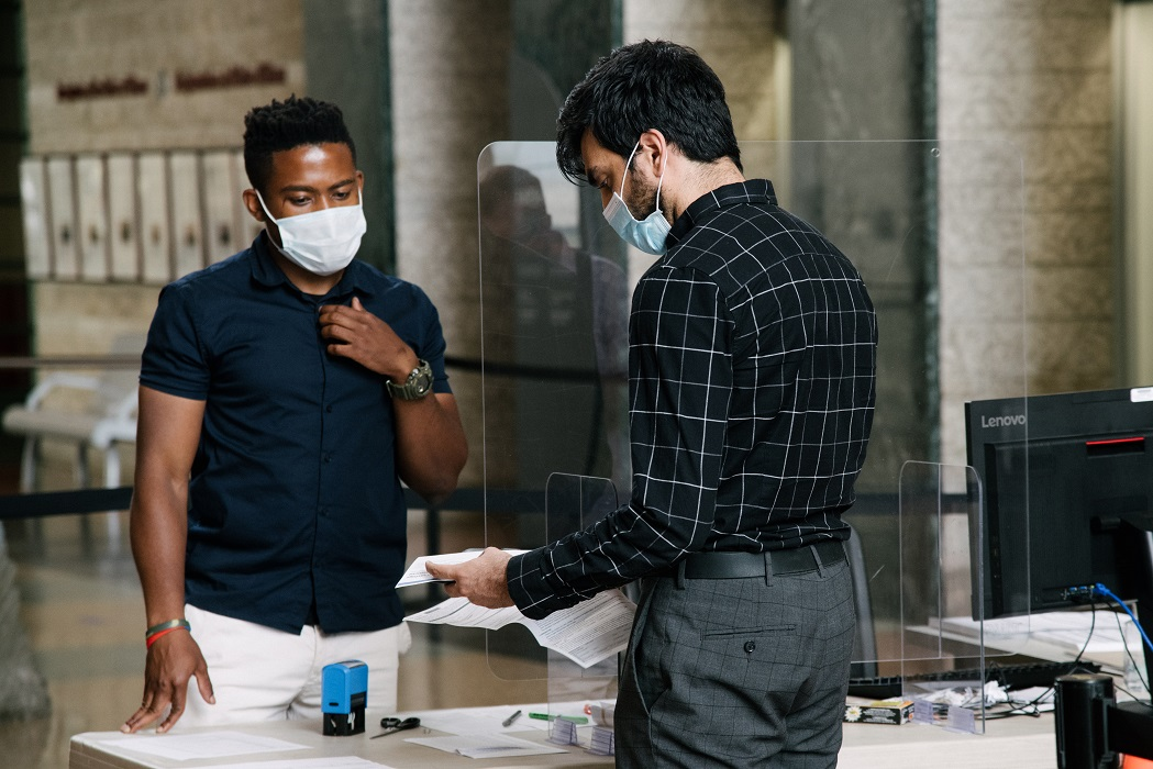 two men, doing business, wearing masks
