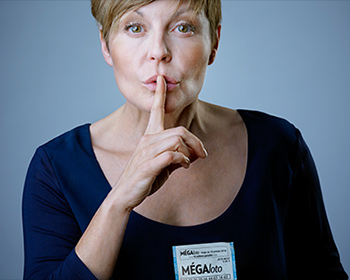 Woman with index finger to her mouth indicating silence