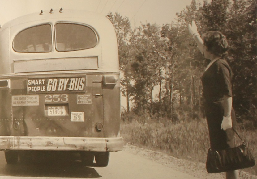 Old photo of a woman and a bus