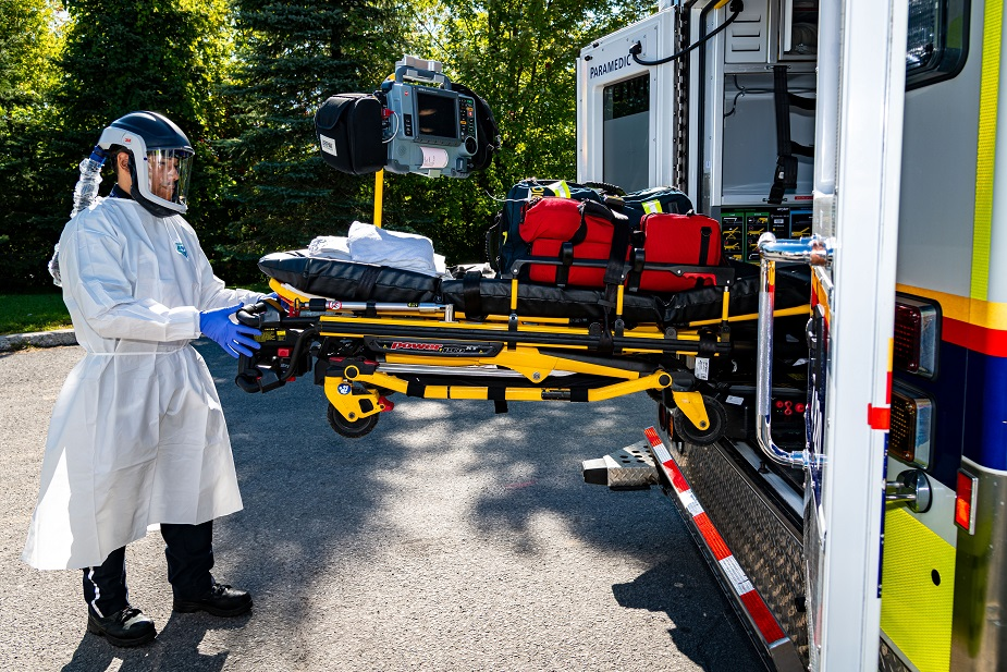 Paramedic wearing protective clothing and loading a stretcher into an ambulance