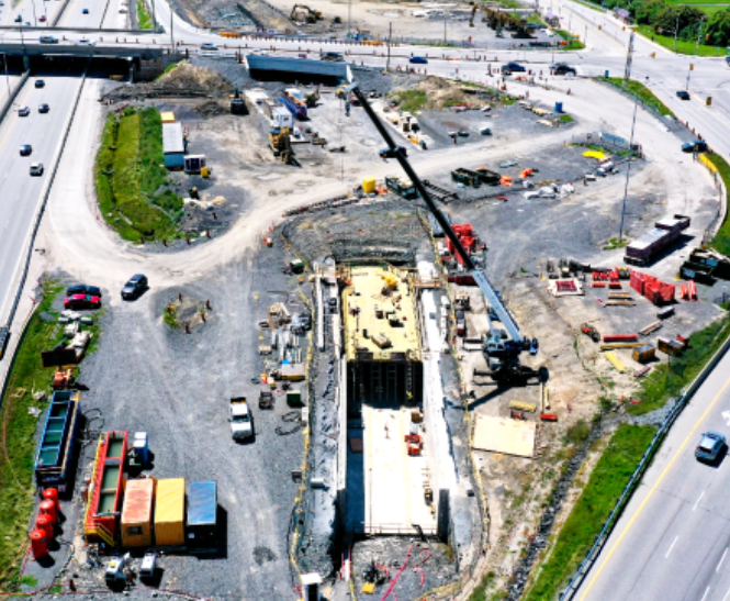 Aerial photograph of future Pinecrest Station with evidence of the guideway trench with a blue crane working in the foreground.