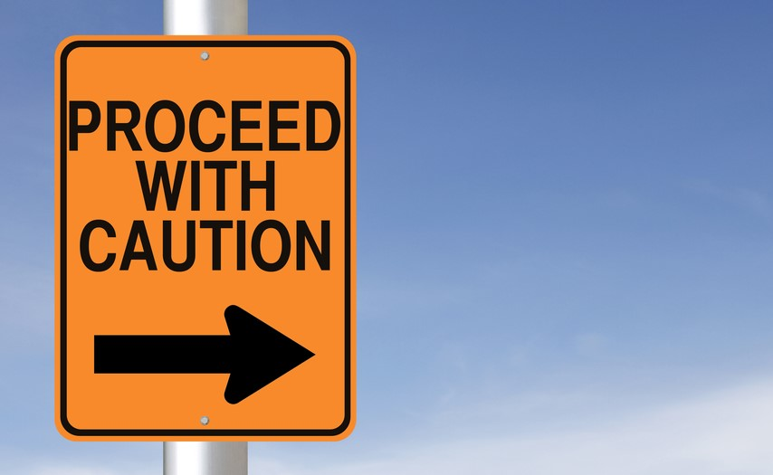 """An orange sign that reads """"proceed with caution"""" against a blue background"""
