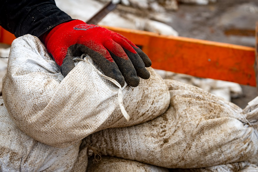 A gloved hand on a pile of sandbags
