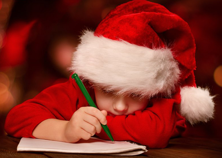 Photograph of a child writing his letter to Santa.