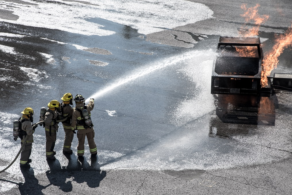 Firefighters extinguish fire with a hose