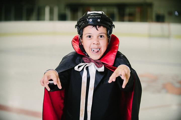 Un garçon patinage et costumé
