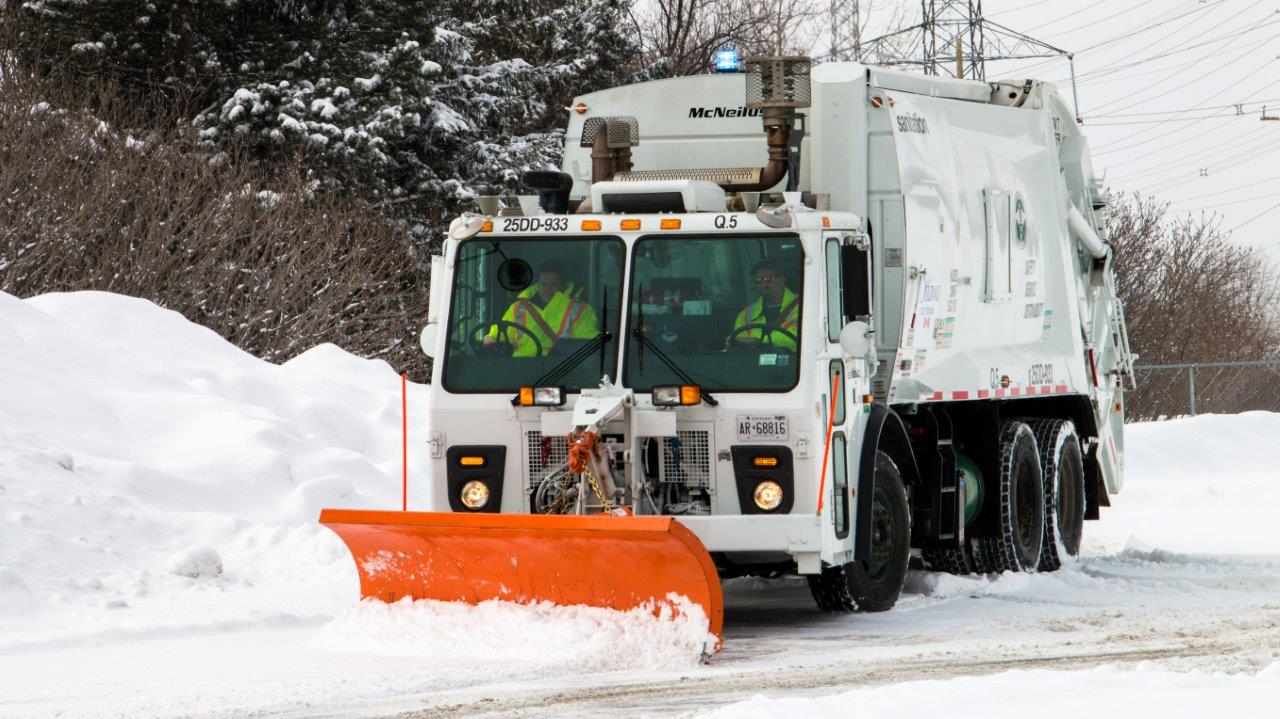 Image of a garbage truck equipped with a snow plow