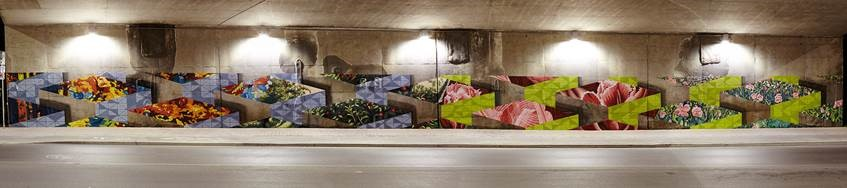 This image shows the west wall of the mural on the Main Street underpass at Highway 417. Painted by artists Dan Bergeron and Gabriel Specter, this mural depicts plant and flower imagery embedded in cubes.