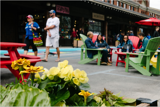 Photographie de l'espace de la rue William montrant un groupe d'amis qui discutent et se reposent sur des chaises Muskoka colorées, un couple qui marche et des fleurs dans une jardinière récemment installée