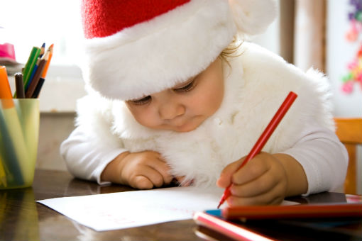 little girl wearing a santa hat and writing a letter