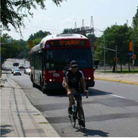 Photograph of a cyclist on Main Street sharing the lane with a vehicle.