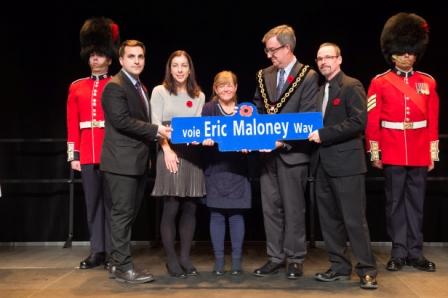 Le maire Watson remet la plaque de rue commémorative à Cynthia Maloney sur scène à la cérémonie à la chandelle pour la désignation de la voie Eric Maloney