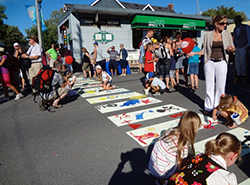 "A 'pop-up' crosswalk being painted by families and children during ""A Taste of Manotick"""