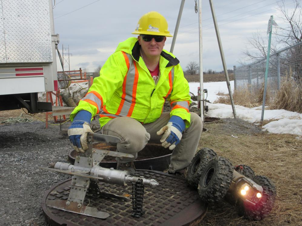 A man in a hard hat, a reflective jacket and work gloves crouches near the access point to a sewer.