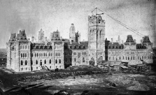 Library and Archives Canada / Samuel McLaughlin / C-018353 / Copyright: Expired Title: Construction of Parliament Buildings, Centre Block, from the roof of the West Block. Main tower in the course of construction.Date: [ca. 1865]