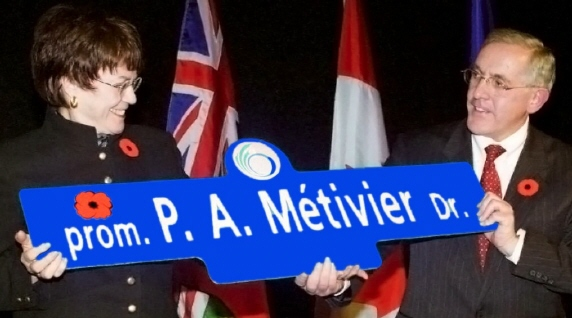 Mayor Bob Chiarelli presenting the commemorative street sign to Madame Justice Monique Métivier on stage at the Candlelight Tribute ceremony for the naming of P.A. Metivier Drive