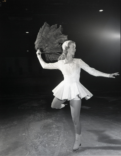 Olympic champion Barbara Ann Scott practicing routine on the ice in costume.