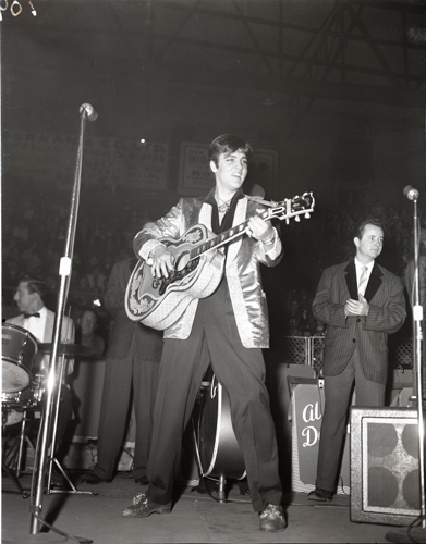 Elvis Presley at the Auditorium. Elvis performing on stage with guitar.