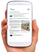 Picture of a hand holding a cell phone displaying the Planning and Development E-newsletter