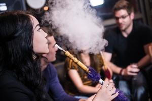 A young woman exhales a cloud of smoke from a hookah in a social setting.
