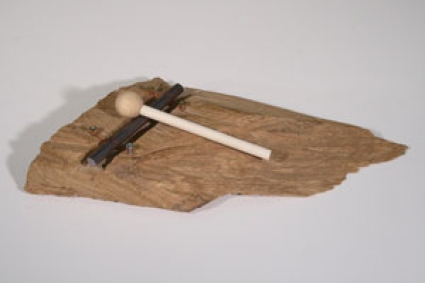 Image of a handmade percussion instrument made of carved wood, a strip of metal and a small mallet.