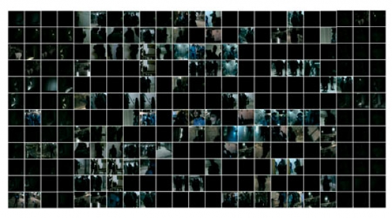 Detail of an installation where two thousand small square photographs are mounted on a wall in a grid. Each photograph is a frame from a censored video of a military exercise conducted at an Israeli prison.