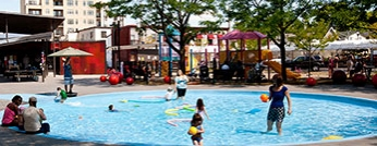 People enjoying a wading pool on a summer day