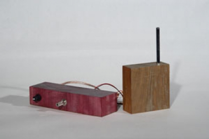 Image of a handmade theremin made from wood and electronic components. A theremin creates sound by sensing the relative position of the user's hands or body.