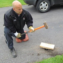 Man gently hitting wood block with sledgehammer to lower water service post