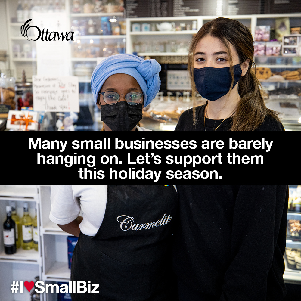 •	Two women wearing masks stand in a café. Many small businesses are barely hanging on. Let's support them this holiday season.