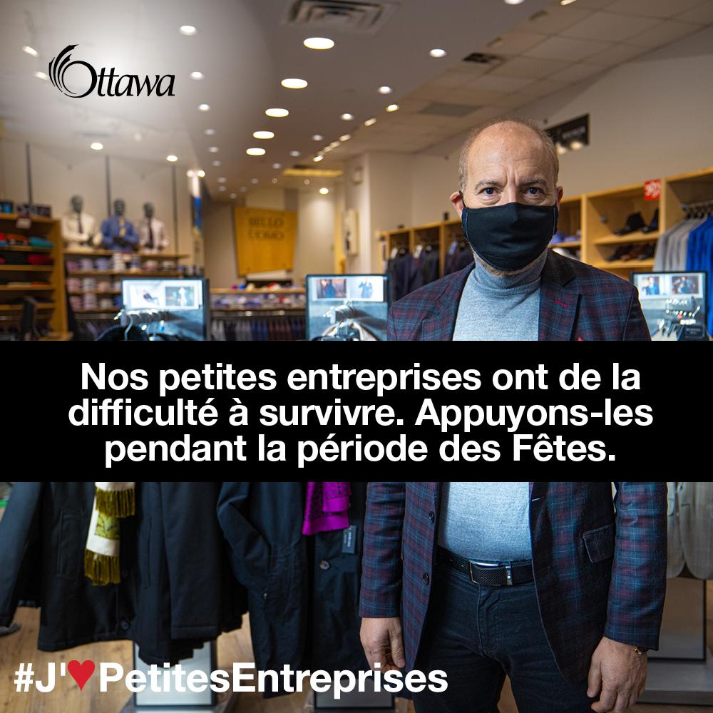 •Un homme qui porte un masque se trouve dans une boutique de vêtements. Nos petites entreprises ont de la difficulté à survivre. Appuyons-les pendant la période des Fêtes.