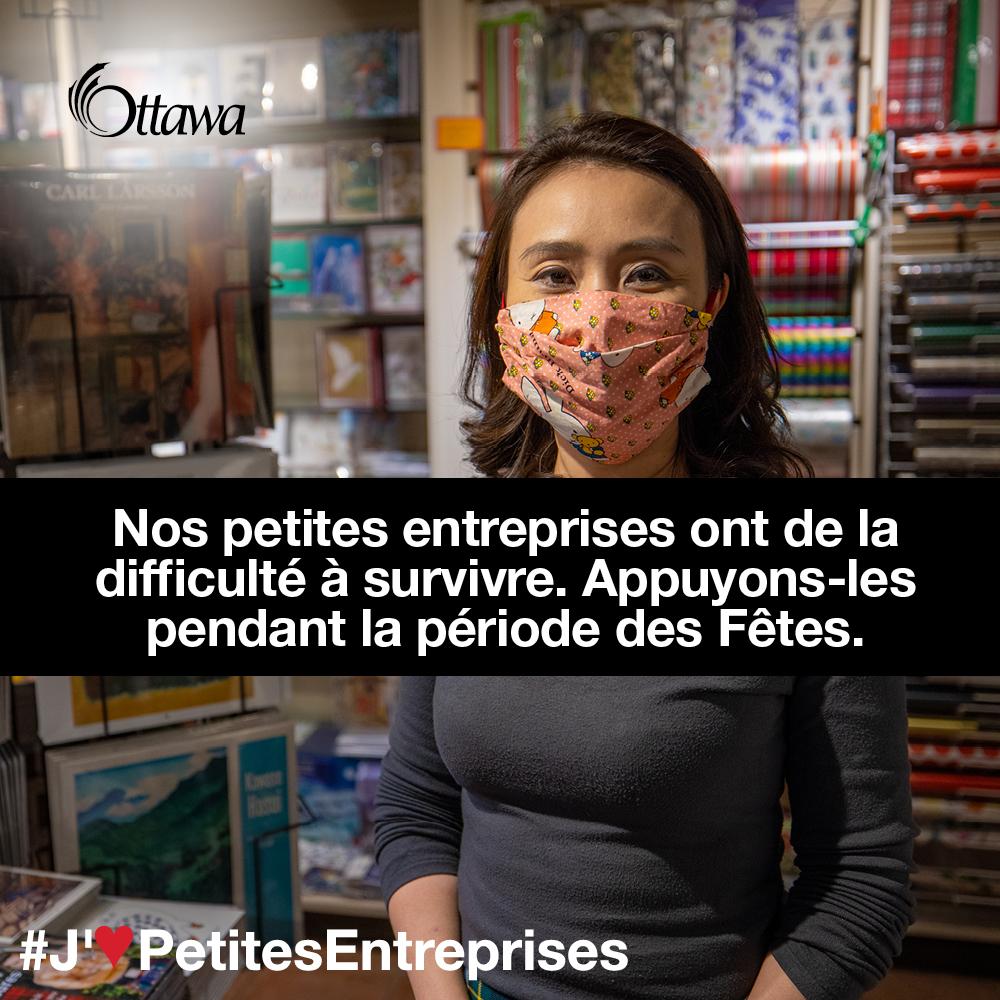 •Une femme qui porte un masque se trouve dans une boutique d'artisanat et de cadeaux. Nos petites entreprises ont de la difficulté à survivre. Appuyons-les pendant la période des Fêtes.