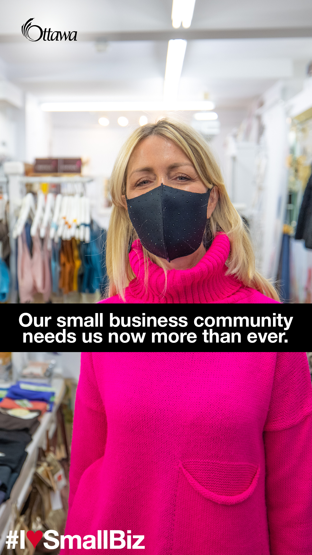 •	A woman wearing a mask stands in a clothing boutique. Our small business community needs us now more than ever.