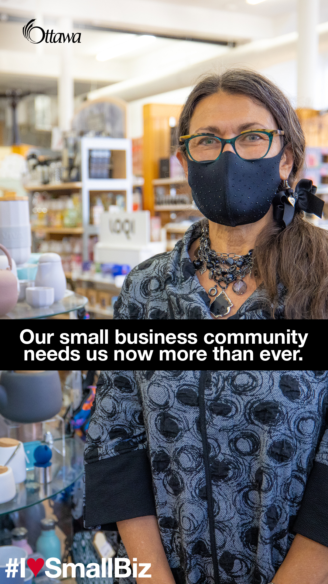A woman wearing a mask stands in a small retail store. Our small business community needs us now more than ever.