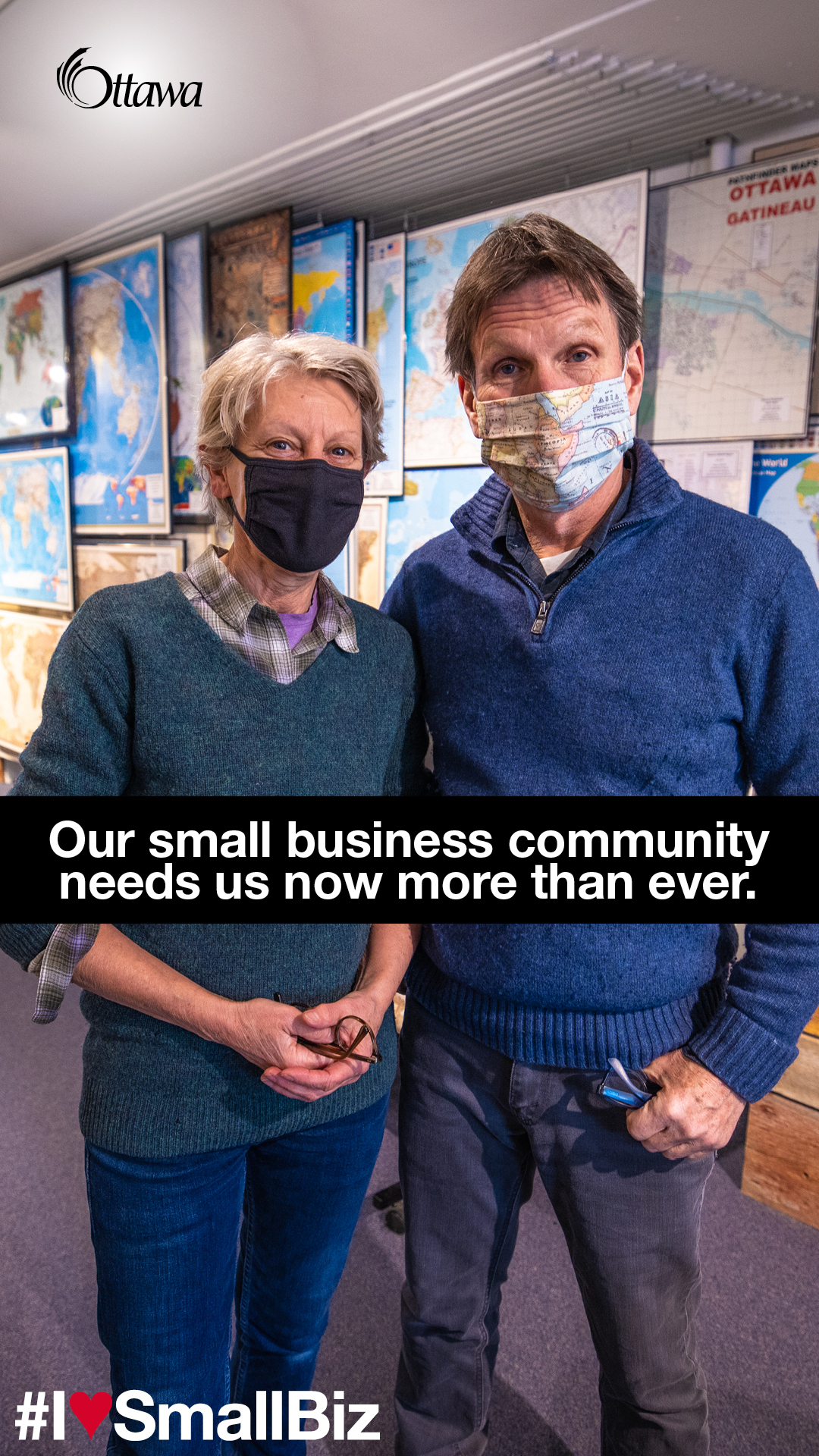•A man and woman wearing a mask stand in a store with maps. Our small business community needs us now more than ever.